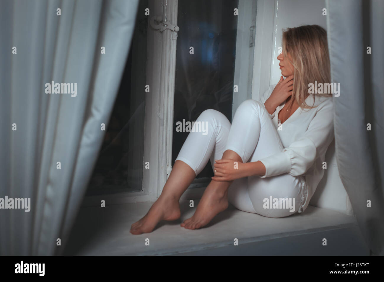 Girl dreams of sitting at the window, she was sad. - Stock Image
