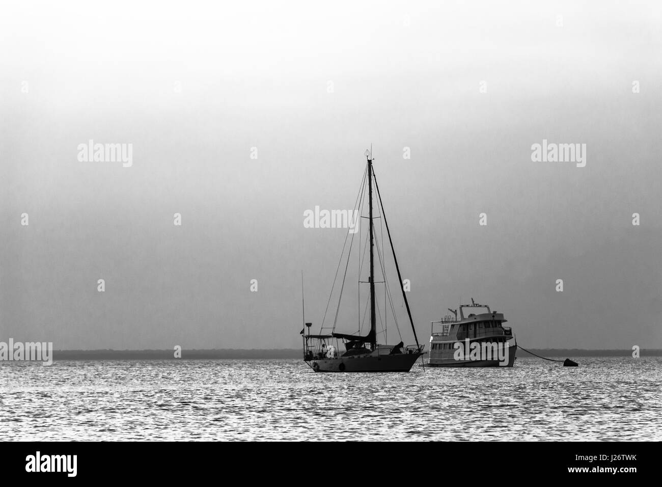 Sailboat and Passenger boat anchored in the Amazon river, Brazil. - Stock Image