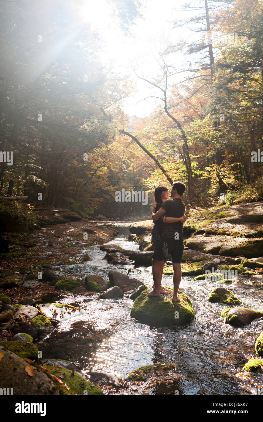 Young couple embracing in a mossy stream - Stock Image
