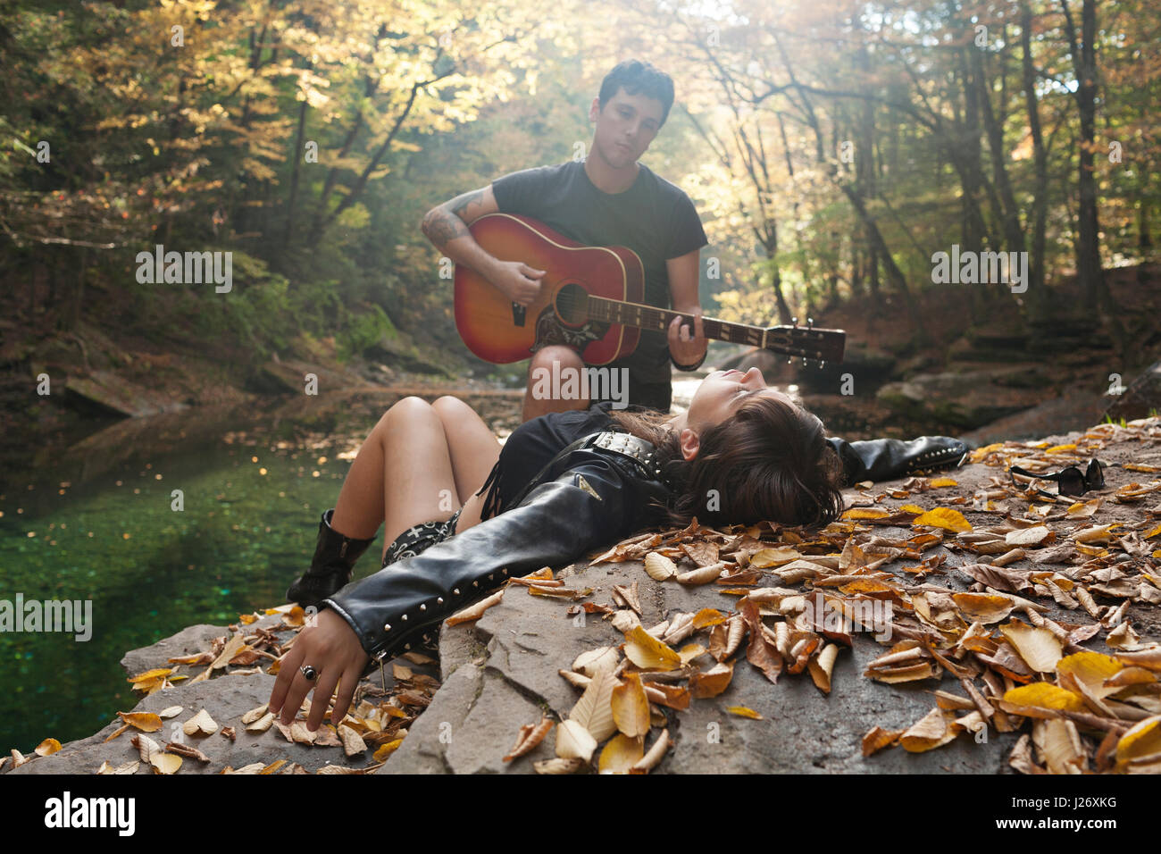 Young man serenading his girlfriend by a stream - Stock Image