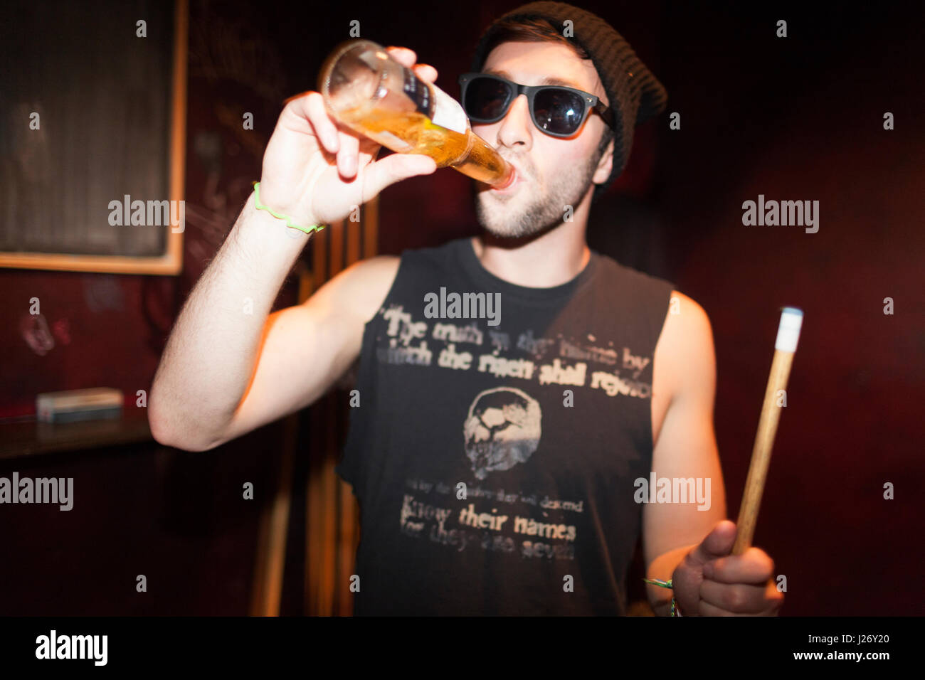 Young man drinking a beer - Stock Image