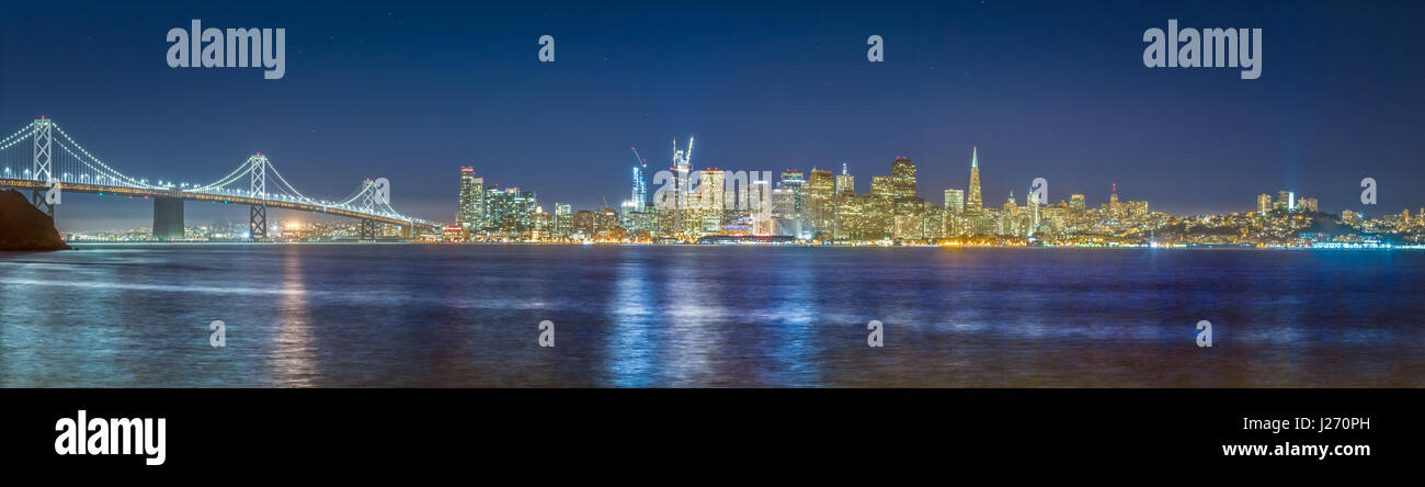 Classic panoramic view of the skyline of San Francisco with famous Oakland Bay Bridge  illuminated in beautiful - Stock Image