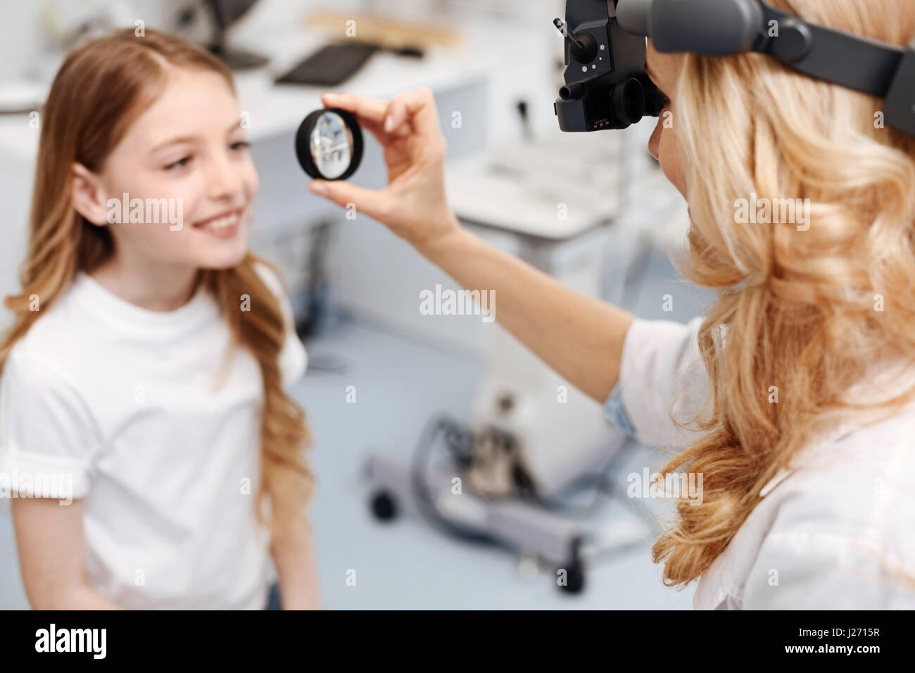 Diligent neat girl trying not to blink - Stock Image