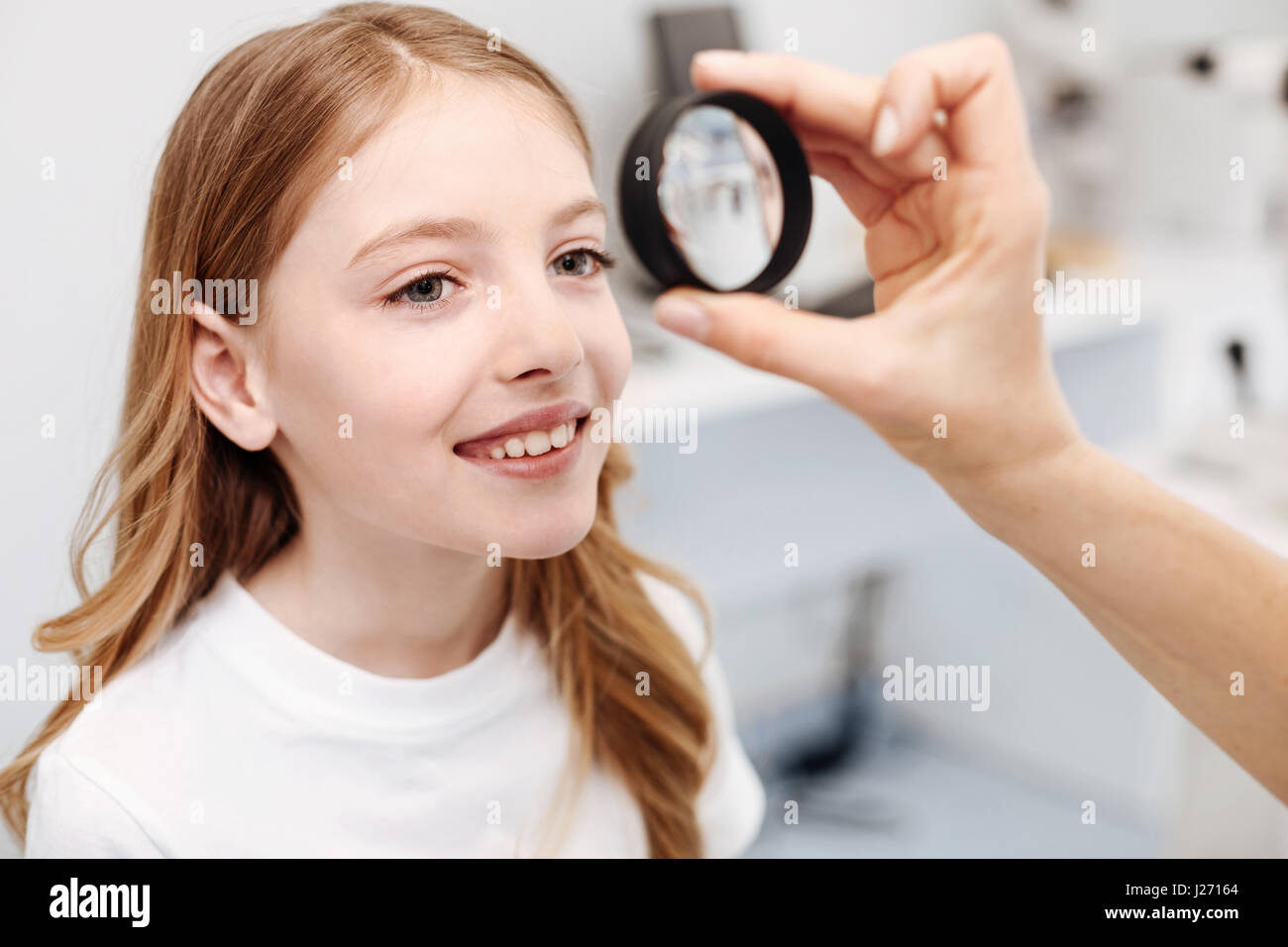 Excellent scrupulous ophthalmologist performing a checkup - Stock Image