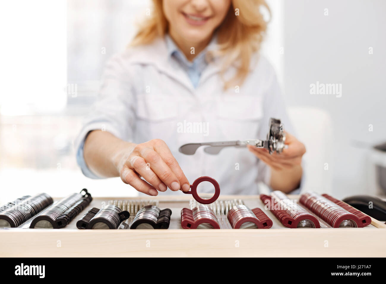 Orderly busy optician taking a lens - Stock Image