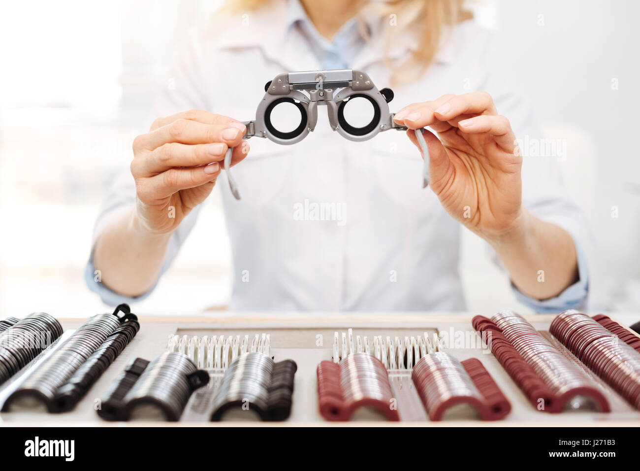 Lovely diligent optician suggesting trial spectacles - Stock Image