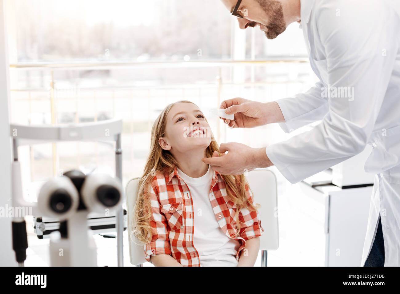 Careful prominent doctor instilling eyedrops - Stock Image