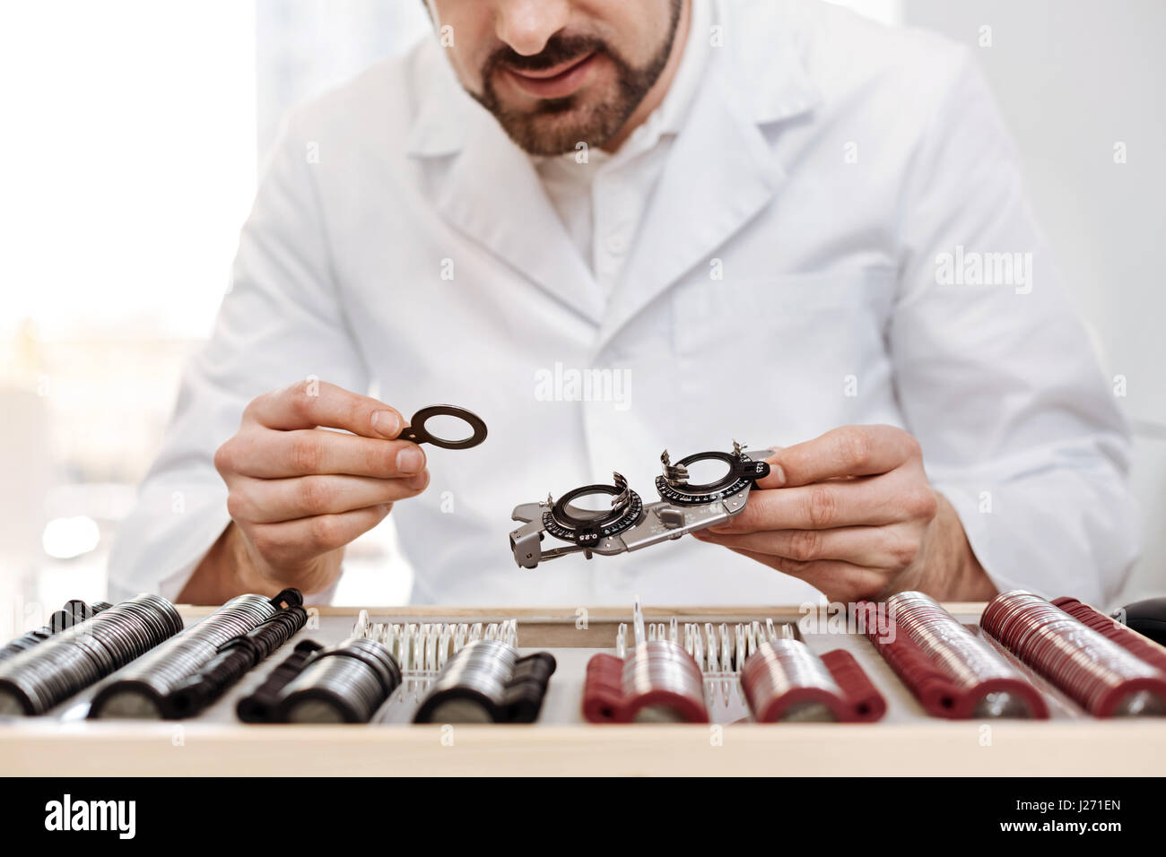 Charming scrupulous ophthalmologist picking right lenses - Stock Image