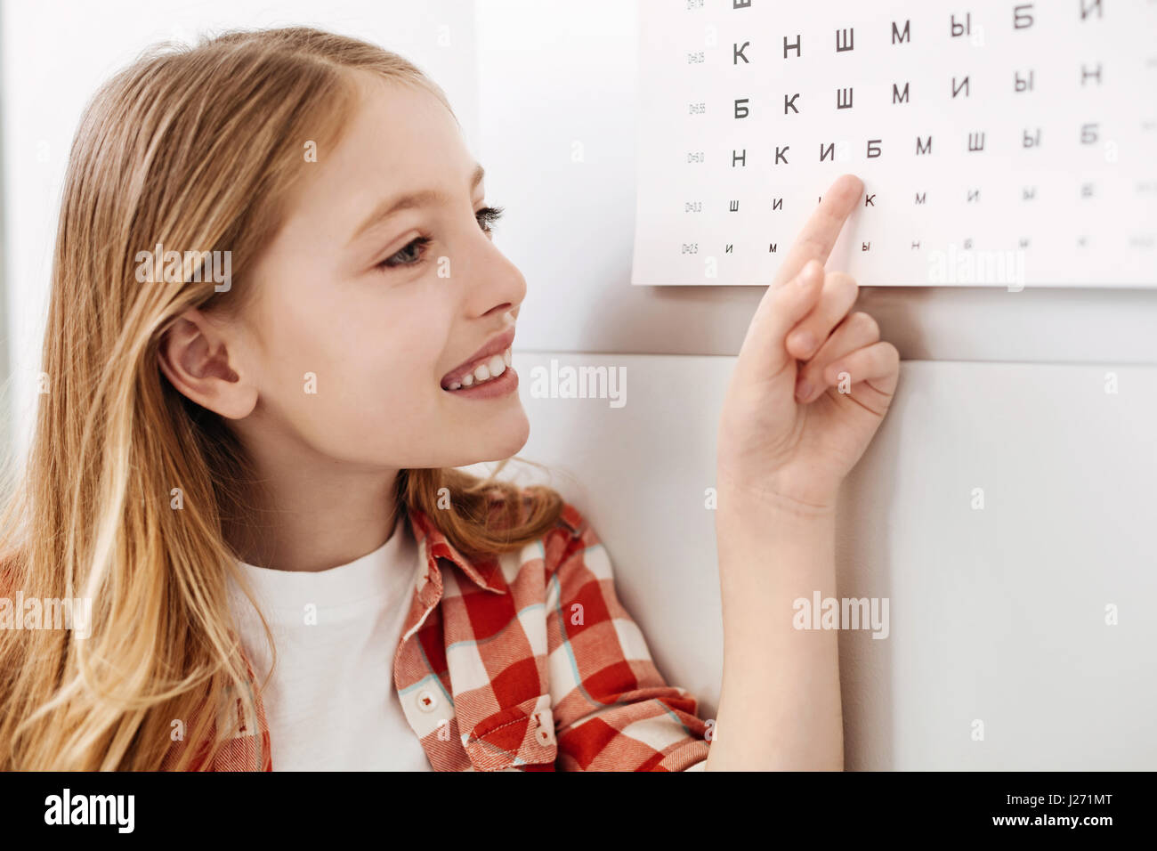 Curious child reading letters from doctors chart - Stock Image