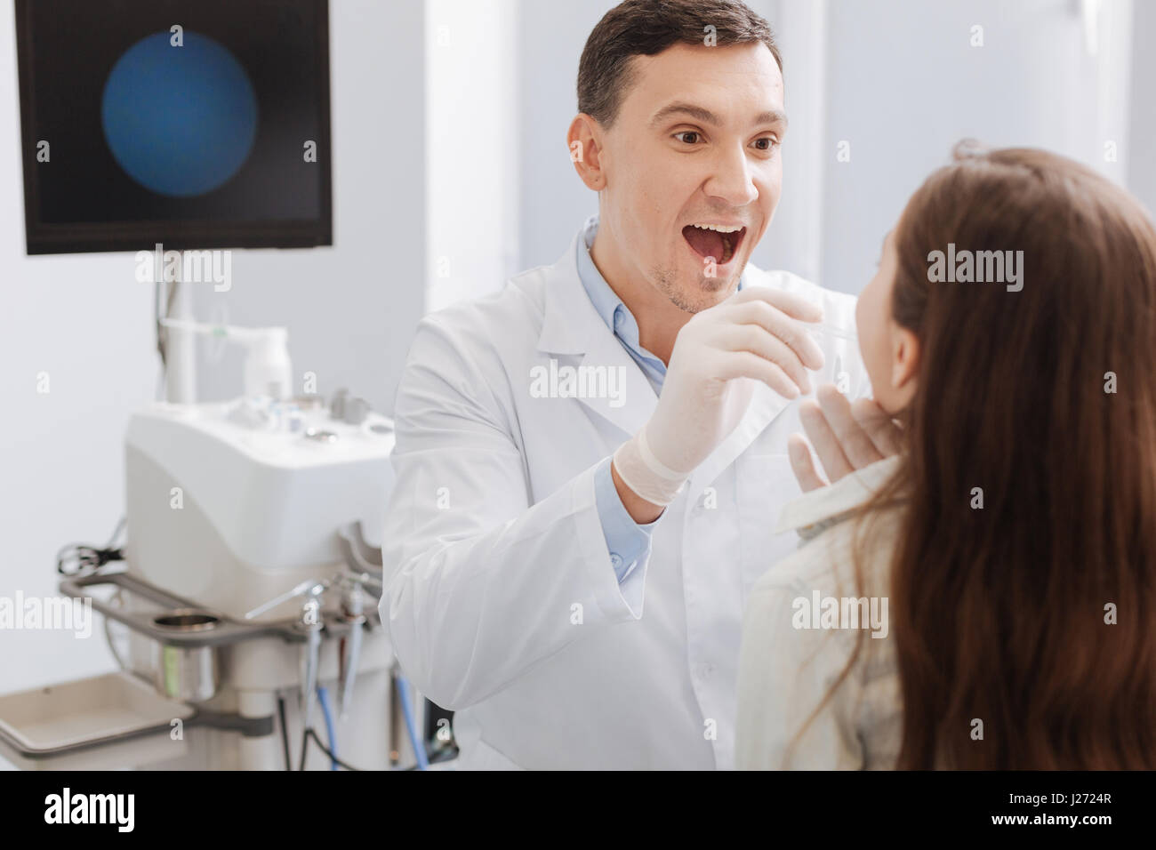 Delighted ENT doctor examining sore throat - Stock Image