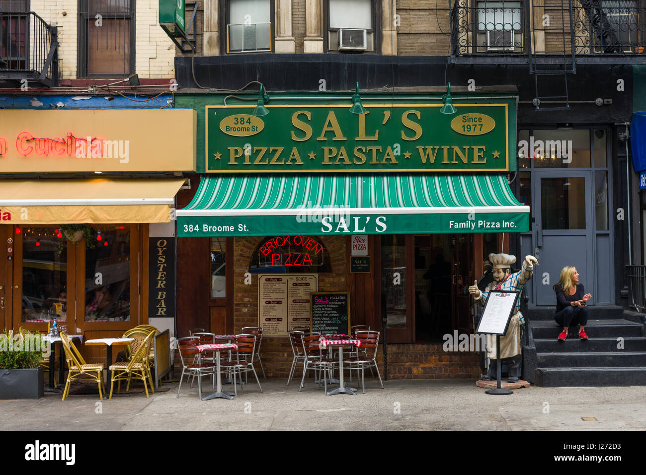 Exterior Of Italian Restaurants With Woman Sat On Steps