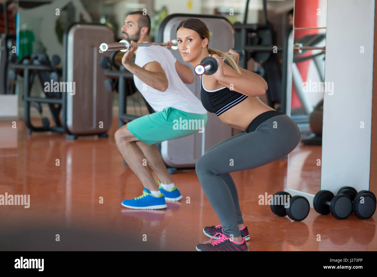 young man and woman with barbell flexing muscles and making shoulder press squat in gym - Stock Image