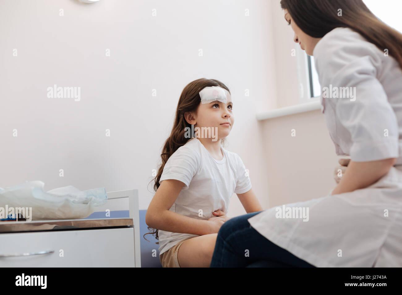 Cheerless sad girl having stomachache - Stock Image