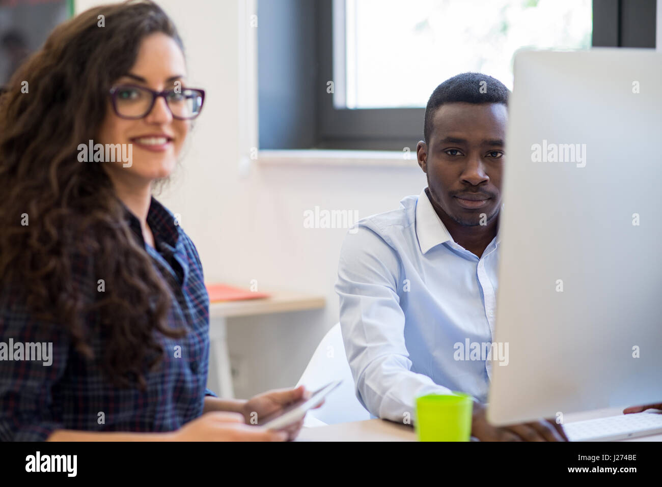 Multiethnic group of happy business people working with laptop computer in office - Stock Image