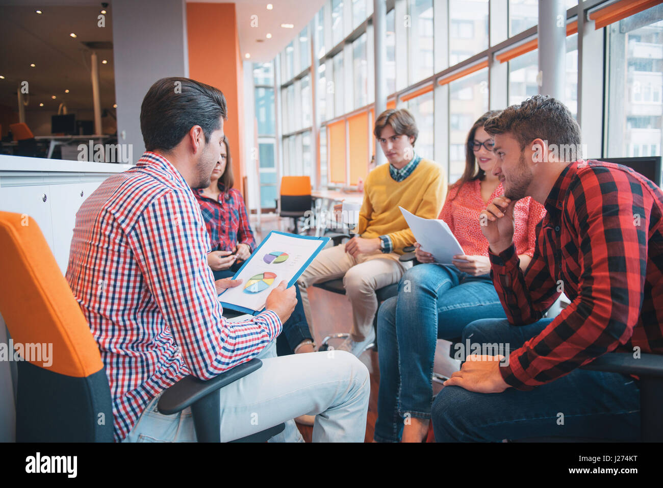 Shot of a group of young business professionals having a meeting. - Stock Image