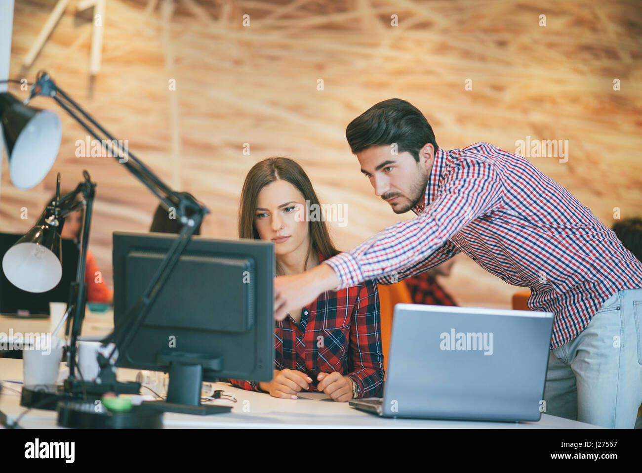 business couple working together on project at modern startup office - Stock Image