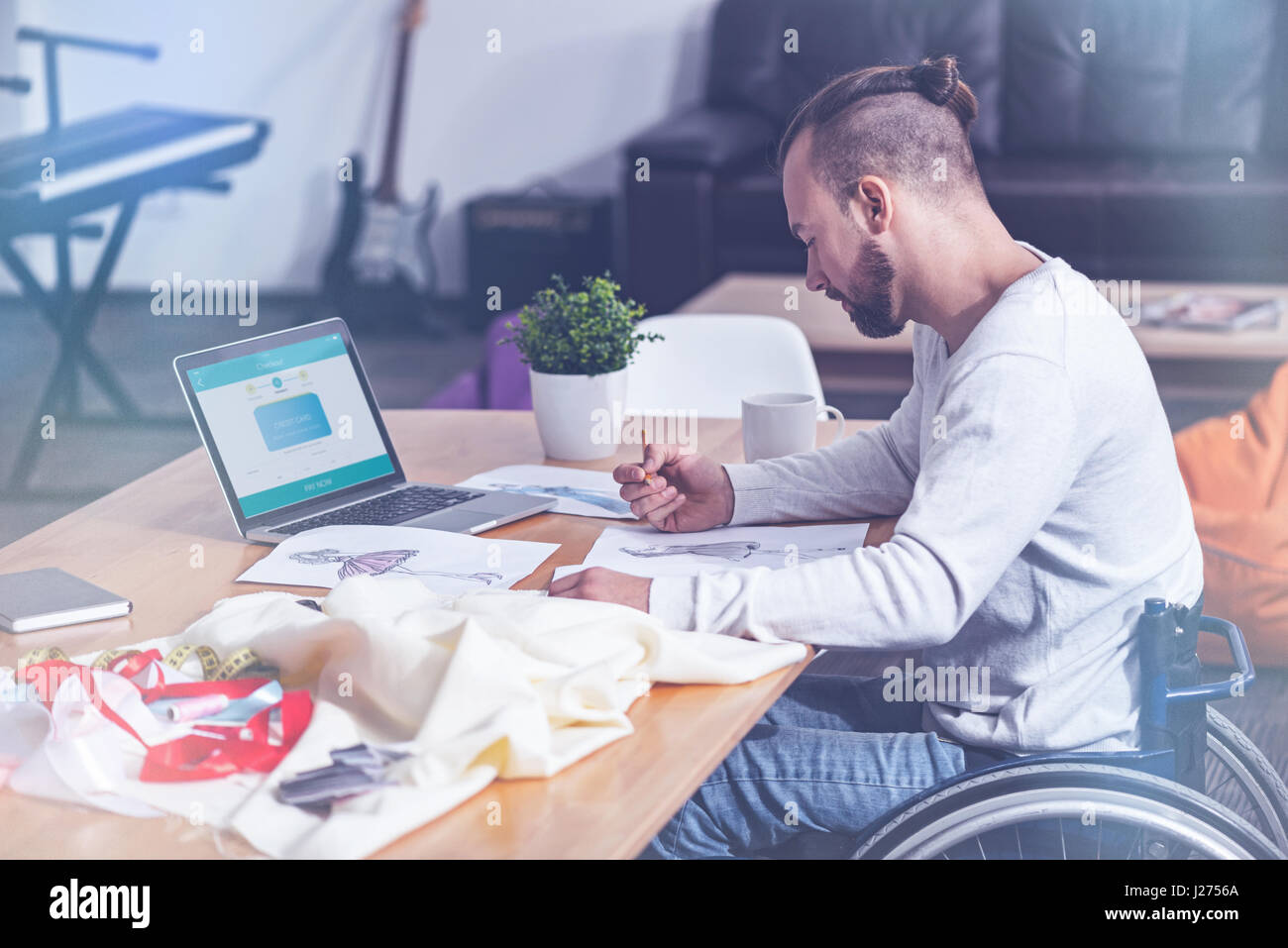 Creative young handicap designing clothes in the studio - Stock Image