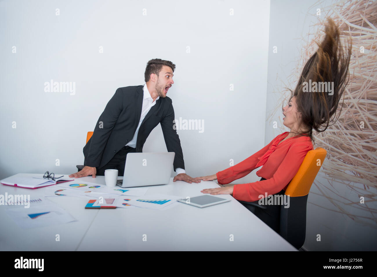 Two angry businesspeople arguing furious showing a negative growth graph - Stock Image