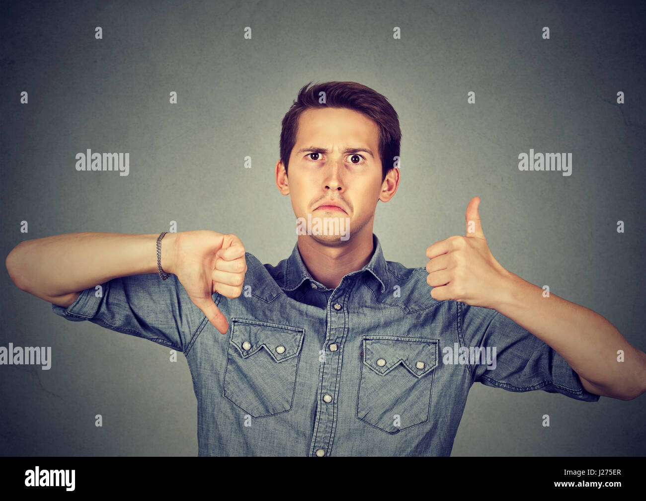Perplexed man with thumbs down thumbs up gesture - Stock Image