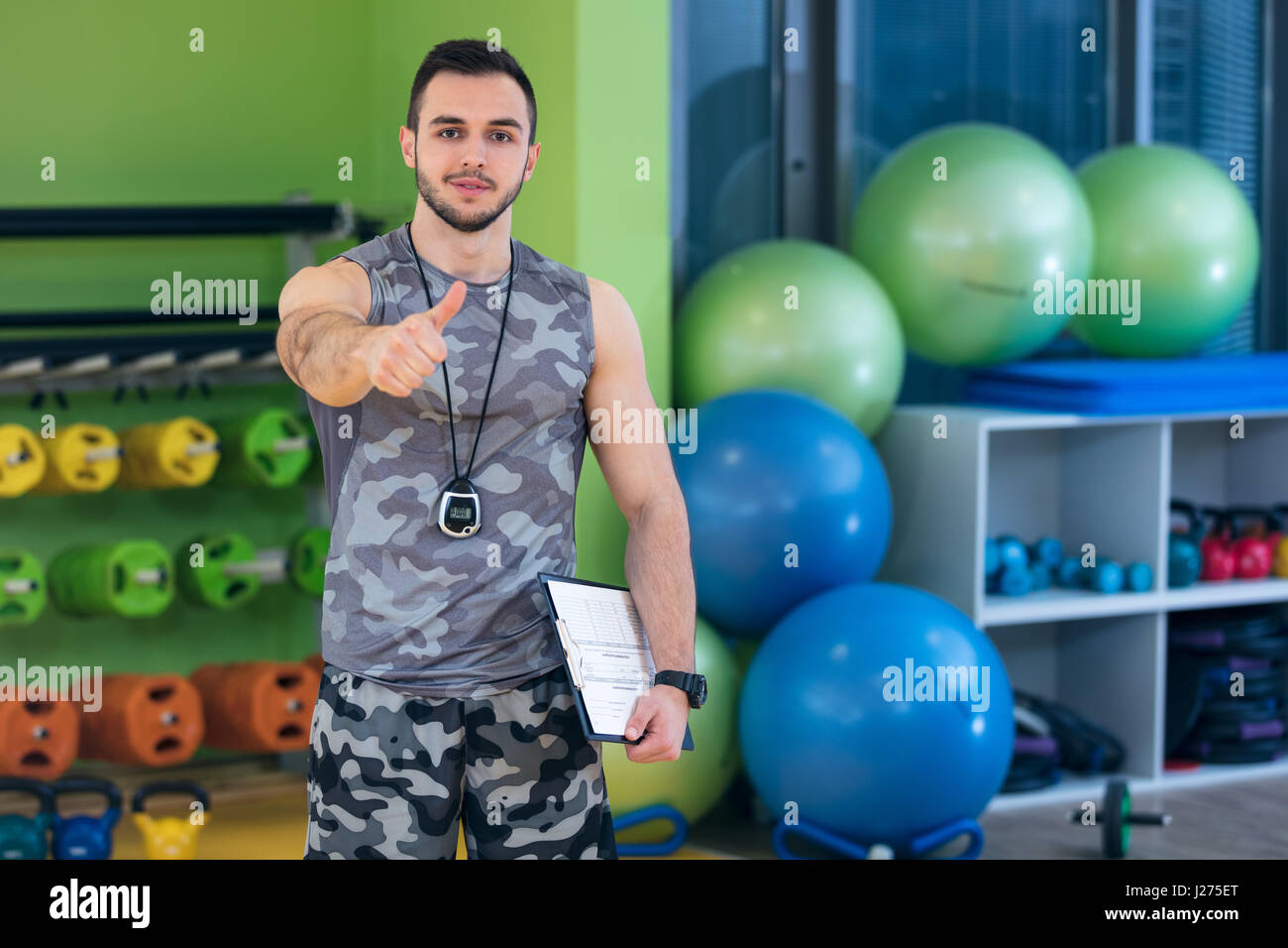 Portrait of a muscular trainer showing thumbs up. Stock Photo