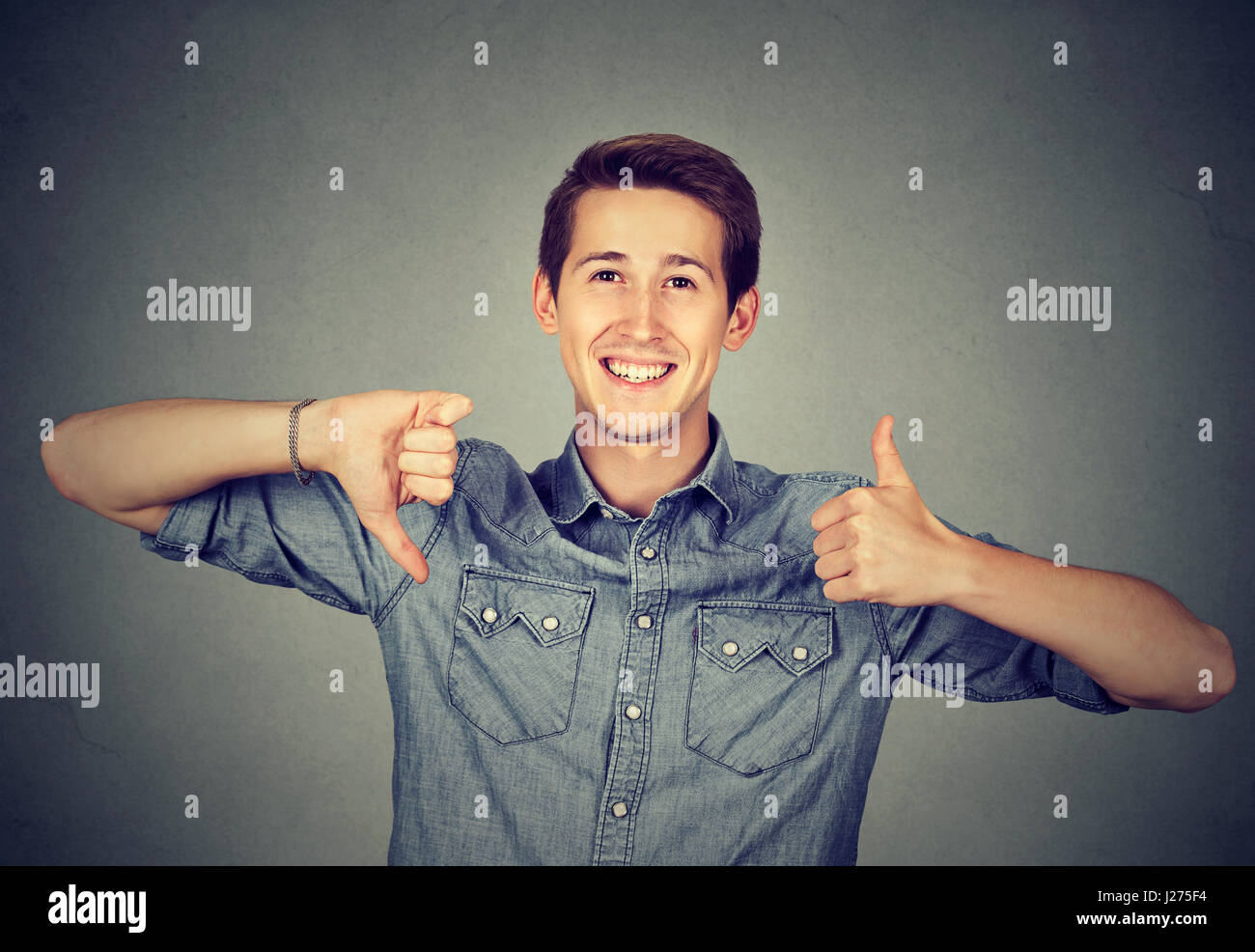 Happy man with thumbs down thumbs up gesture - Stock Image
