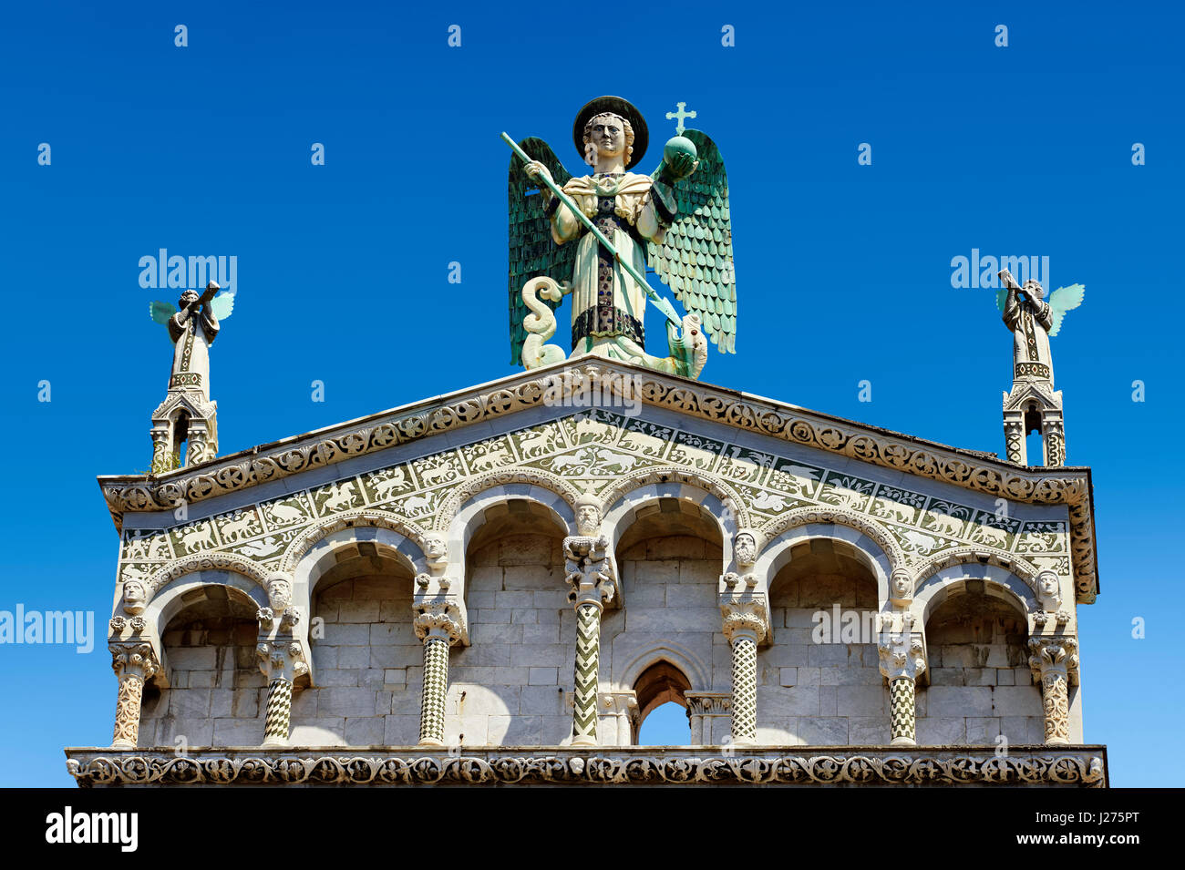 Close up of the statue of St Michele of the 13th century Romanesque facade of the San Michele in Foro,  Lucca, Italy - Stock Image