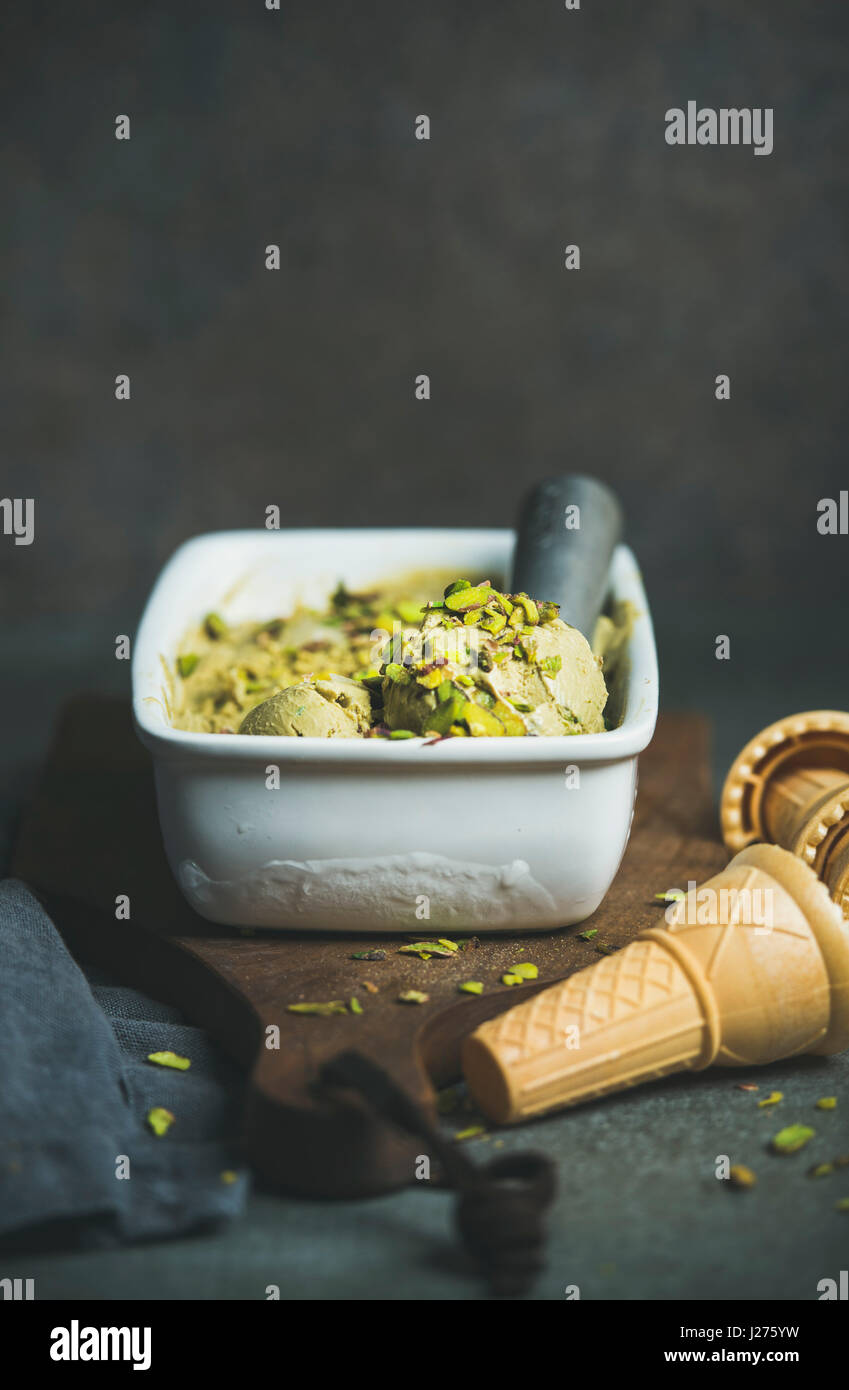 Homemade pistachio ice cream in ceramic mold with metal scooper, crashed pistachio nuts and waffle cones over concrete - Stock Image
