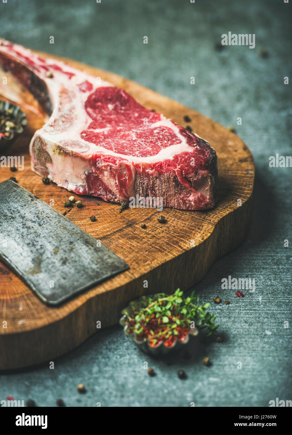 Dry aged raw beef rib eye steak with bone, butcher meat chopping knife and spices on wooden board over grey concrete Stock Photo