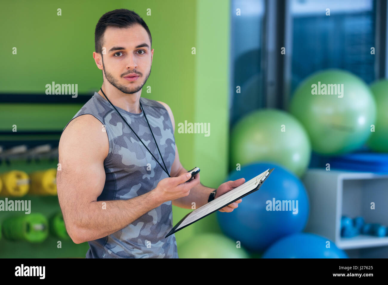 Portrait of a muscular trainer writing on clipboard - Stock Image