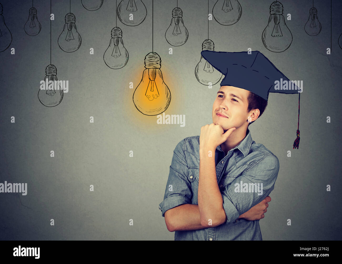Thoughtful graduate student young man in cap gown looking up at bright light bulb thinking isolated gray wall background. - Stock Image