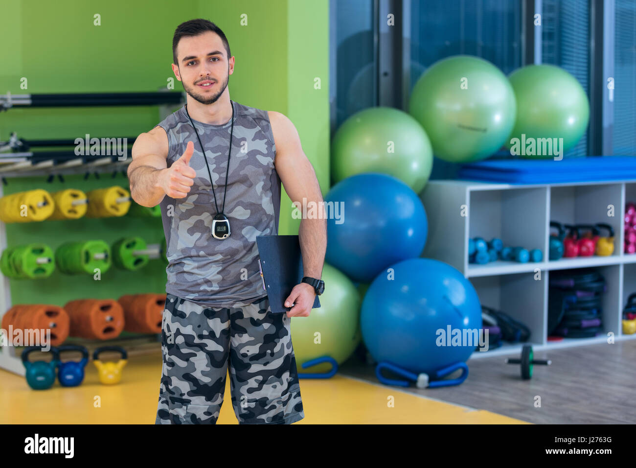 Portrait of a muscular trainer showing thumbs up. - Stock Image