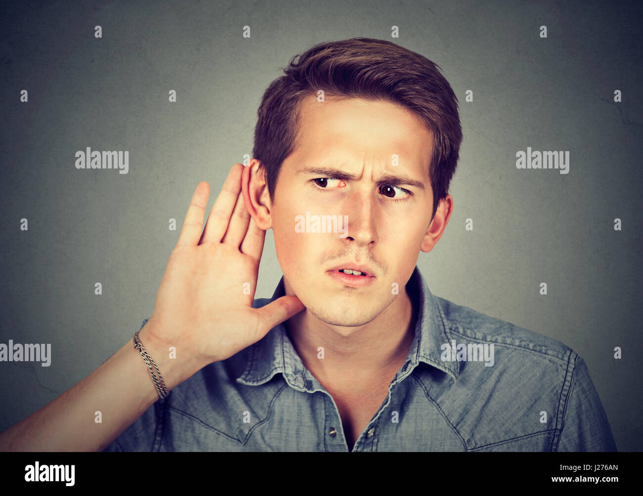 Closeup portrait hard of hearing man placing hand on ear asking someone to speak up or listening carefully to a - Stock Image