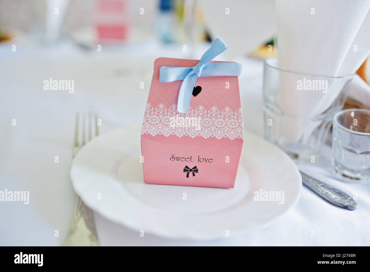 Small box with candies at dish on wedding table of guests with sign ...