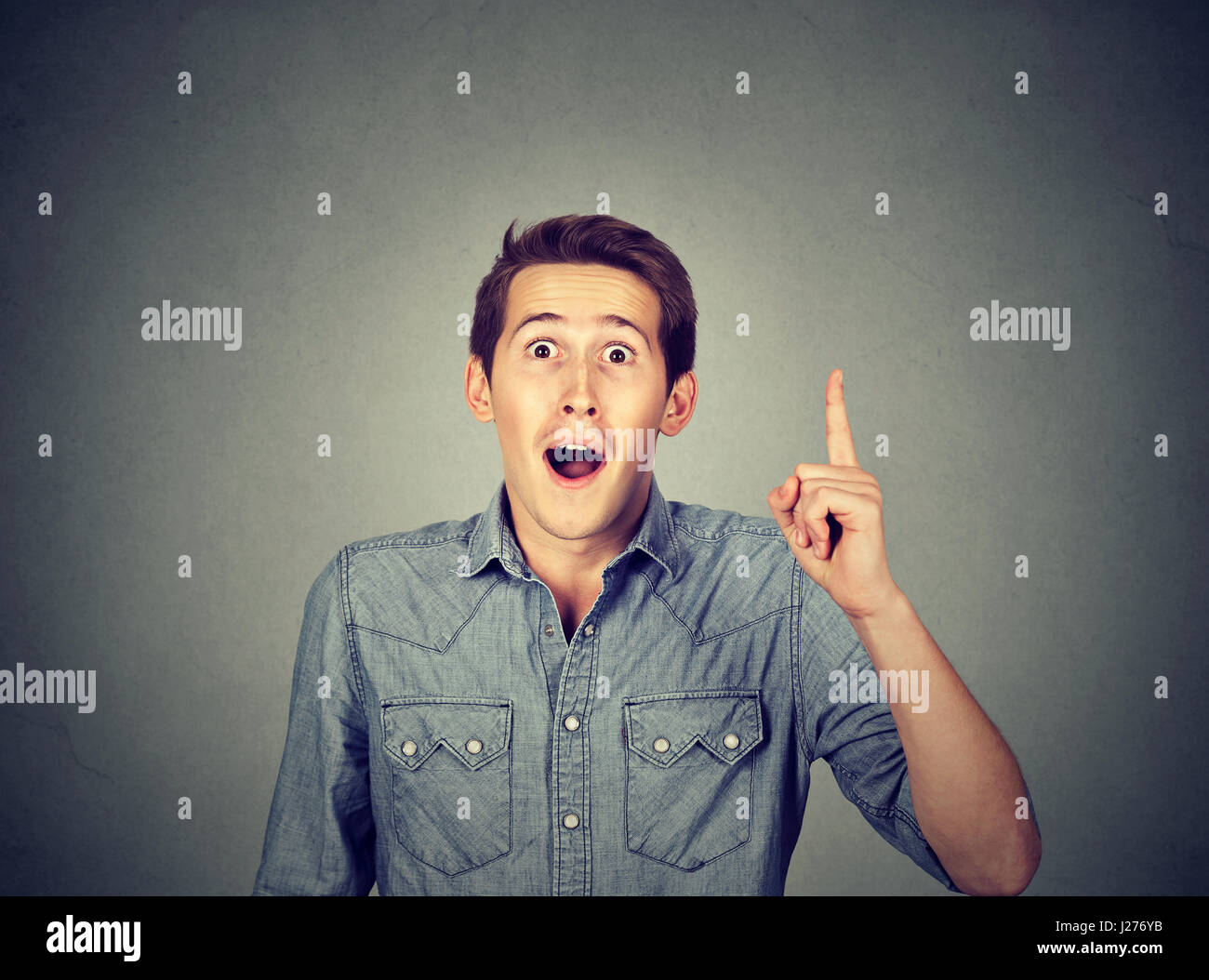 Young man has idea, pointing with finger up isolated on gray background. Smart guy solved a problem. Positive face - Stock Image
