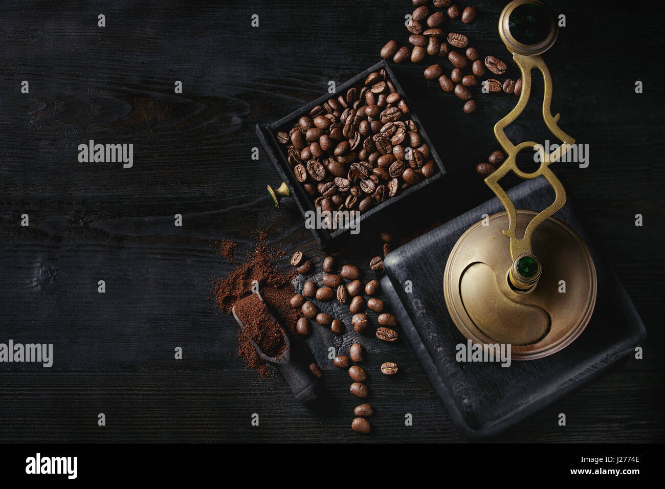 Roasted coffee beans and grind coffee in wood box with vintage coffee grinder and scoop over black wooden burnt - Stock Image