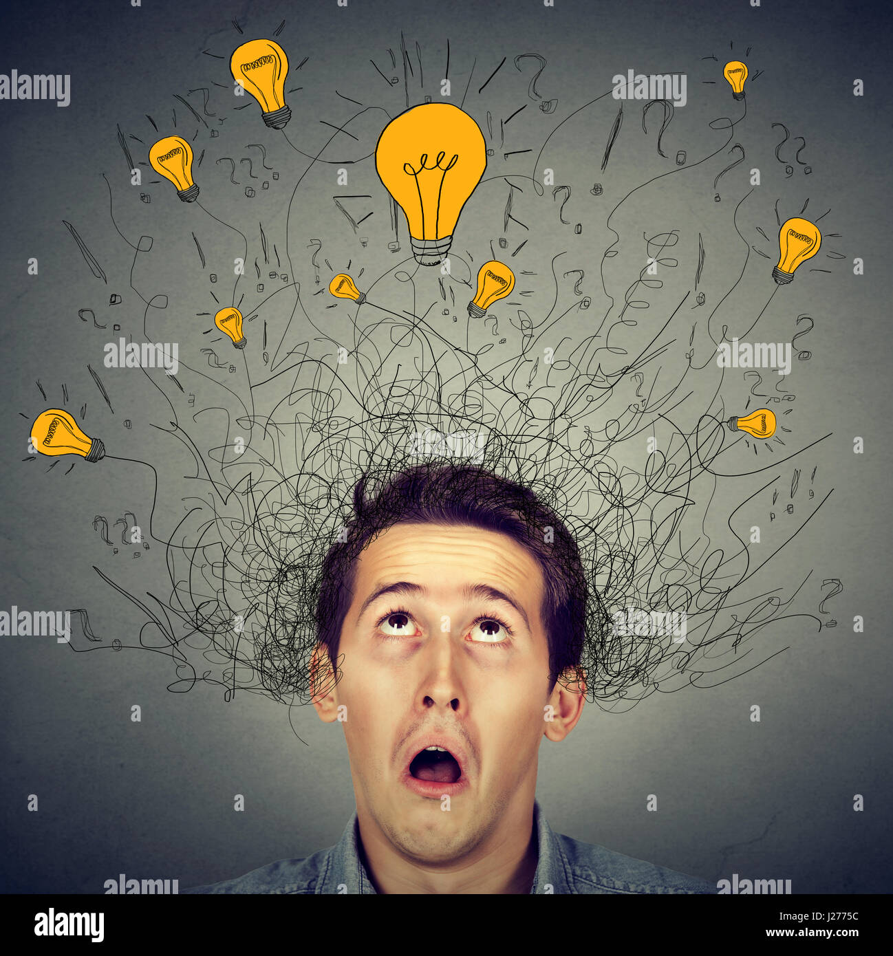Surprised man with many ideas light bulbs above head looking up isolated on gray wall background. Eureka creativity - Stock Image
