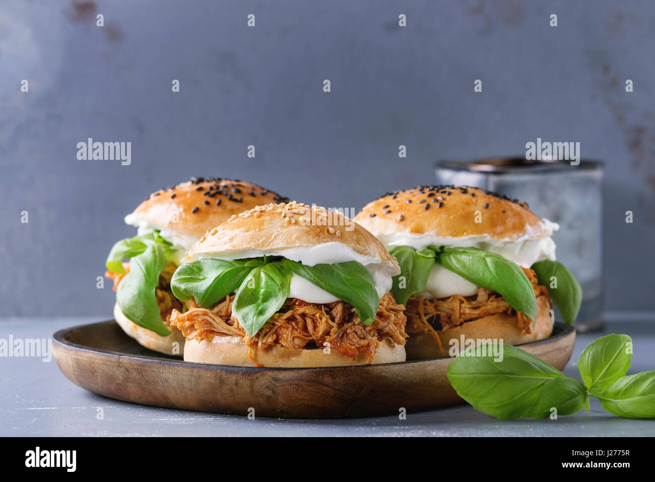 Homemade mini burgers with pulled chicken, basil, mozzarella cheese and yogurt sauce on wooden plate over gray texture - Stock Image