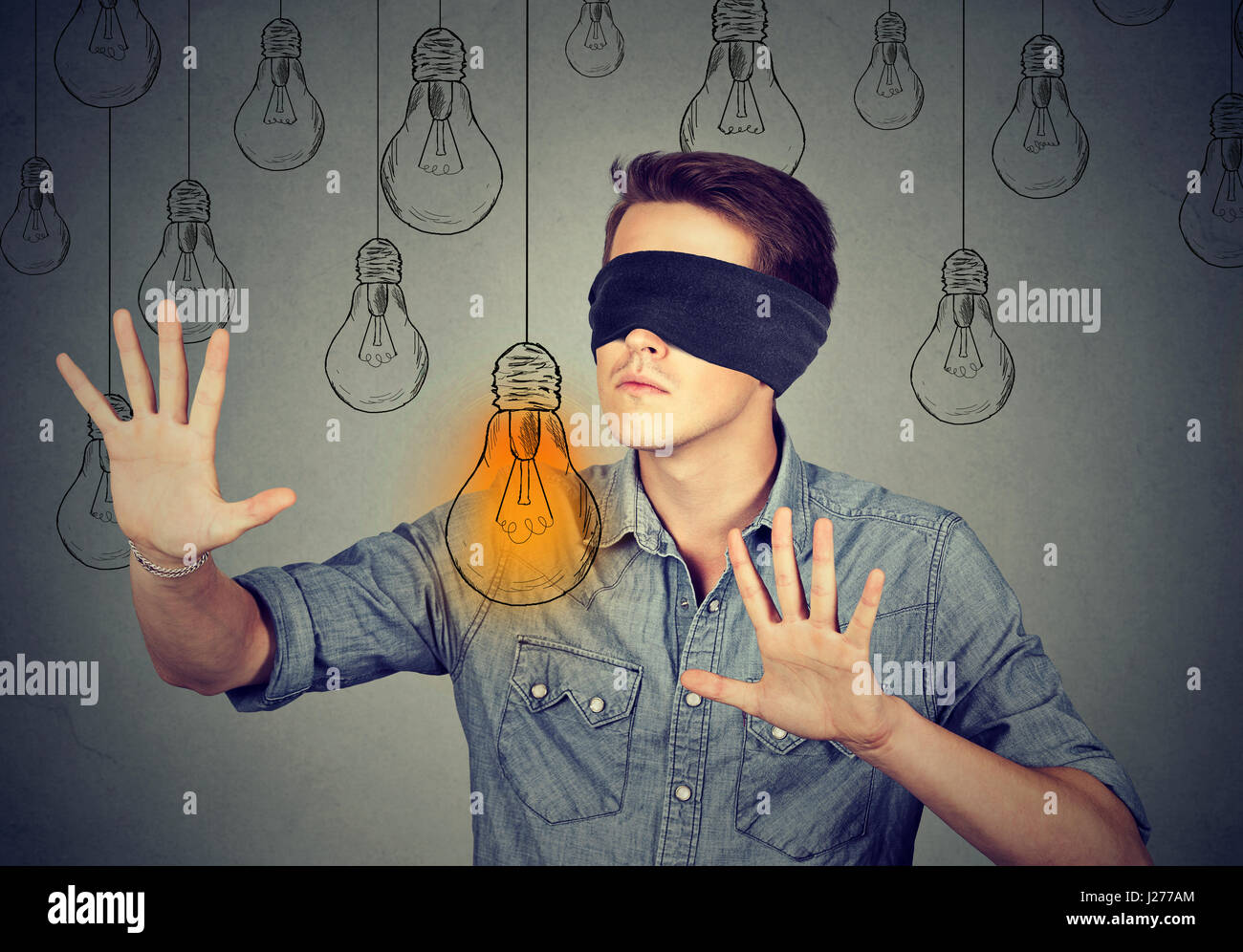 Blindfolded young man walking through light bulbs searching for bright idea - Stock Image