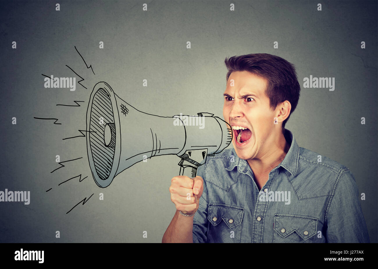Side portrait angry young man holding screaming in megaphone isolated on gray background. Negative face expression - Stock Image
