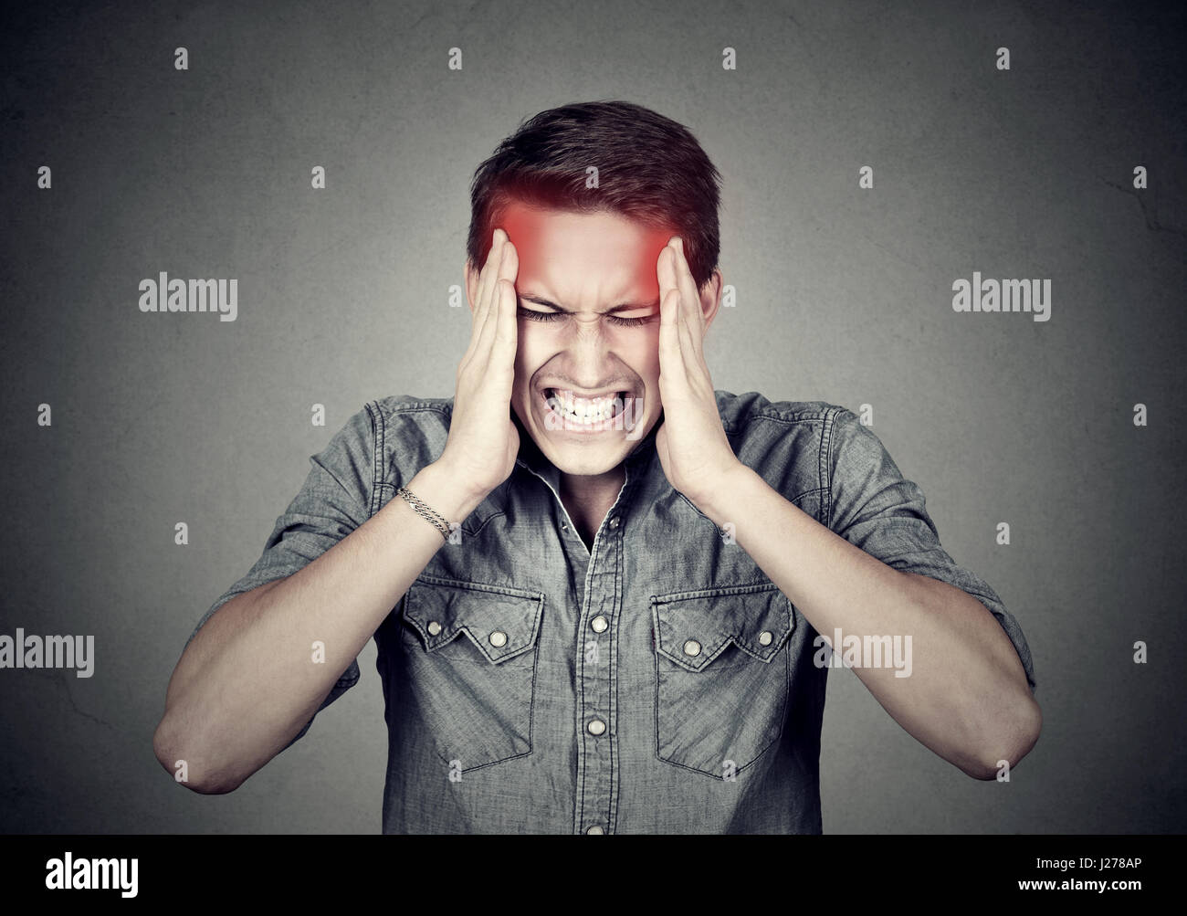 Stressed man with headache isolated on gray wall background - Stock Image