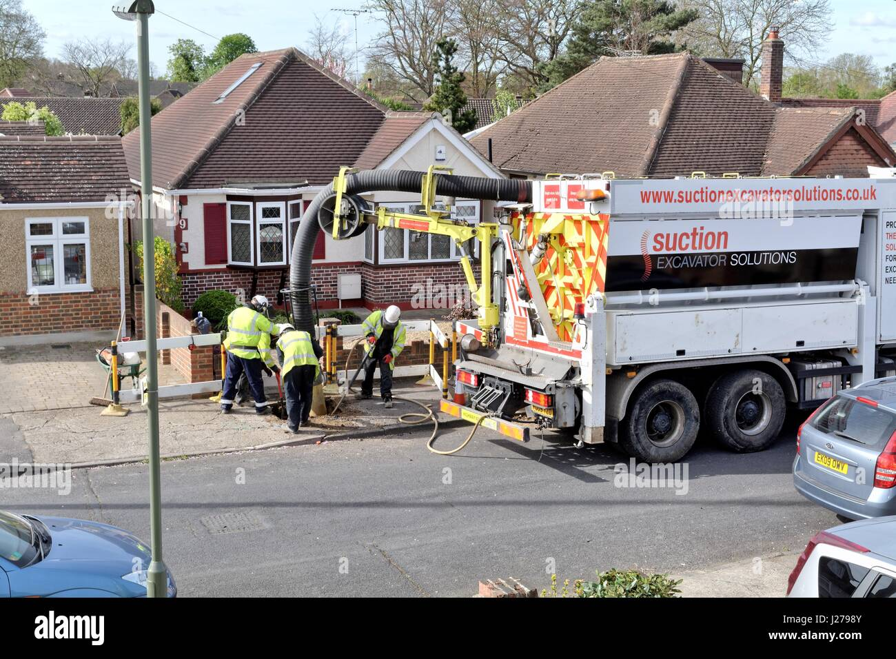 Large suction lorry excavating  a hole in a suburban pavement in Shepperton Surrey UK - Stock Image