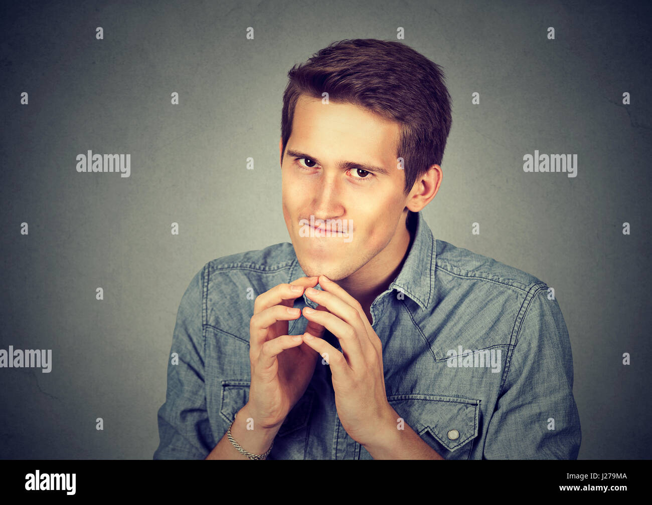 Sneaky scheming young man plotting something isolated on gray wall background. Negative human emotion facial expression - Stock Image