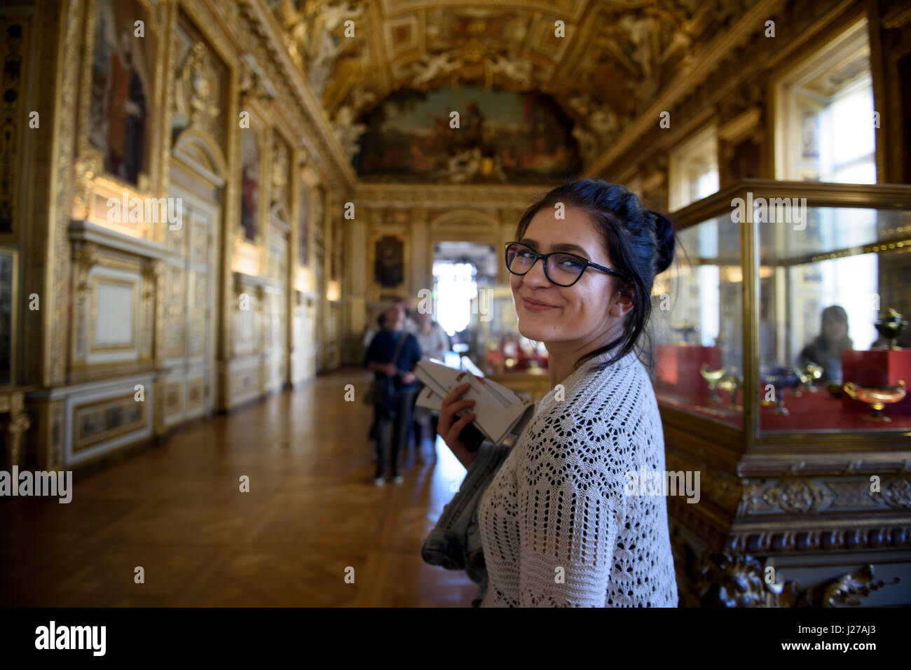 Young woman tourist is visiting the Apollo Gallery at the Louvre museum in Paris, France. - Stock Image