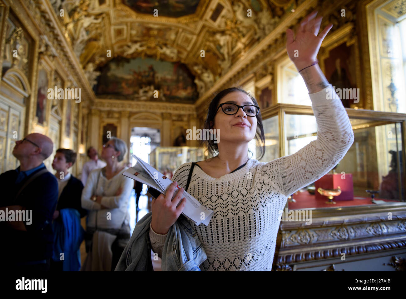 Young woman is waving inside the Apollo Gallery at the Louvre museum in Paris, France. - Stock Image