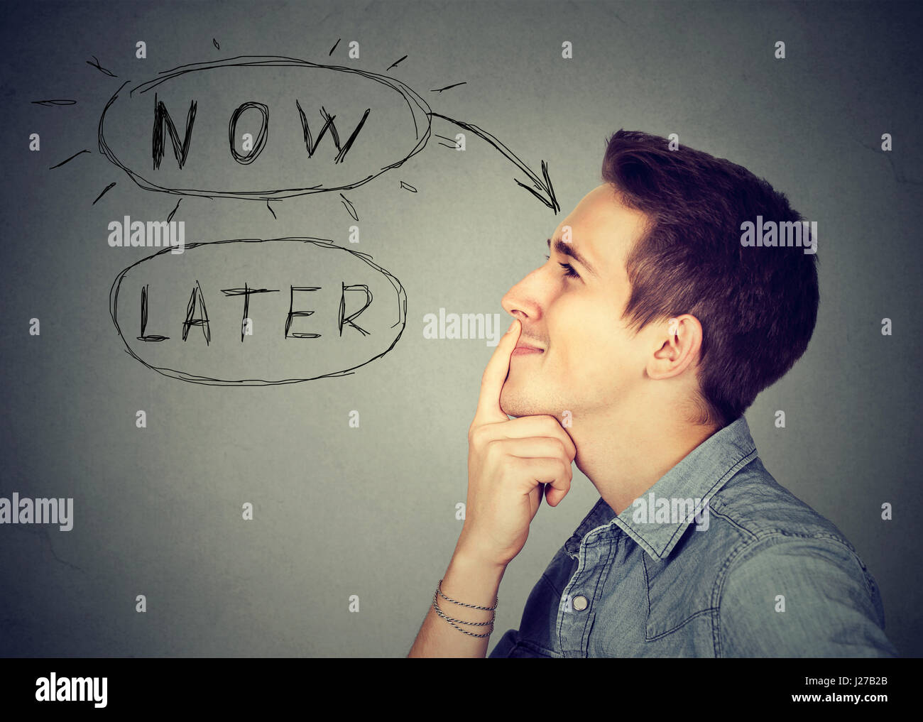Now or later. Side profile happy man thinking looking up making up his mind isolated on gray wall background. Human - Stock Image