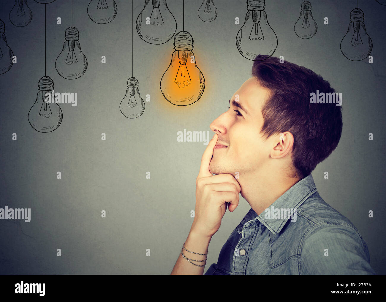 Thinking man looking up with light idea bulb above head isolated on gray wall background - Stock Image