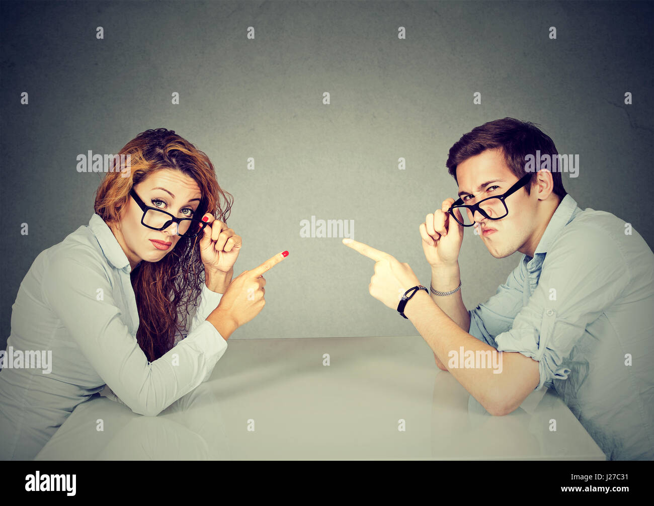 man and woman, couple pointing fingers at each other, blaming each other for the problem - Stock Image