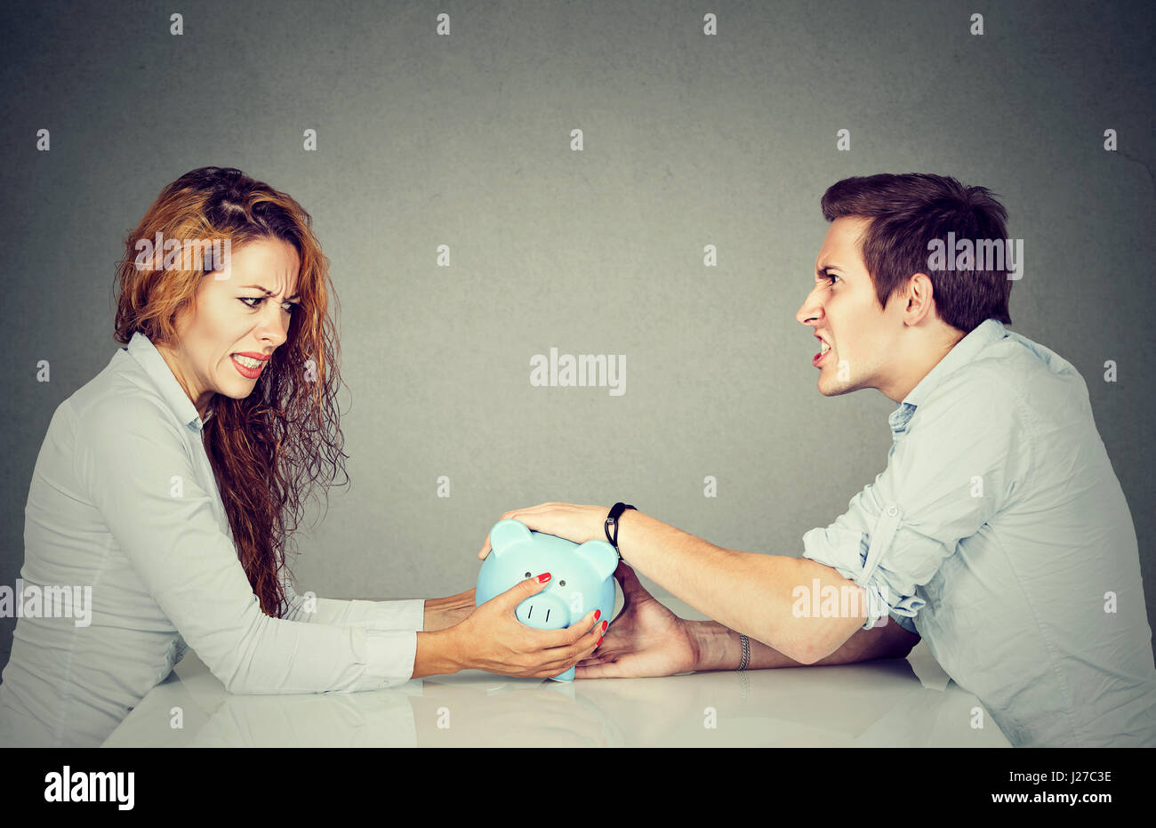 Finances in divorce concept. Wife and husband can not make settlement holding piggy bank sitting at table looking - Stock Image