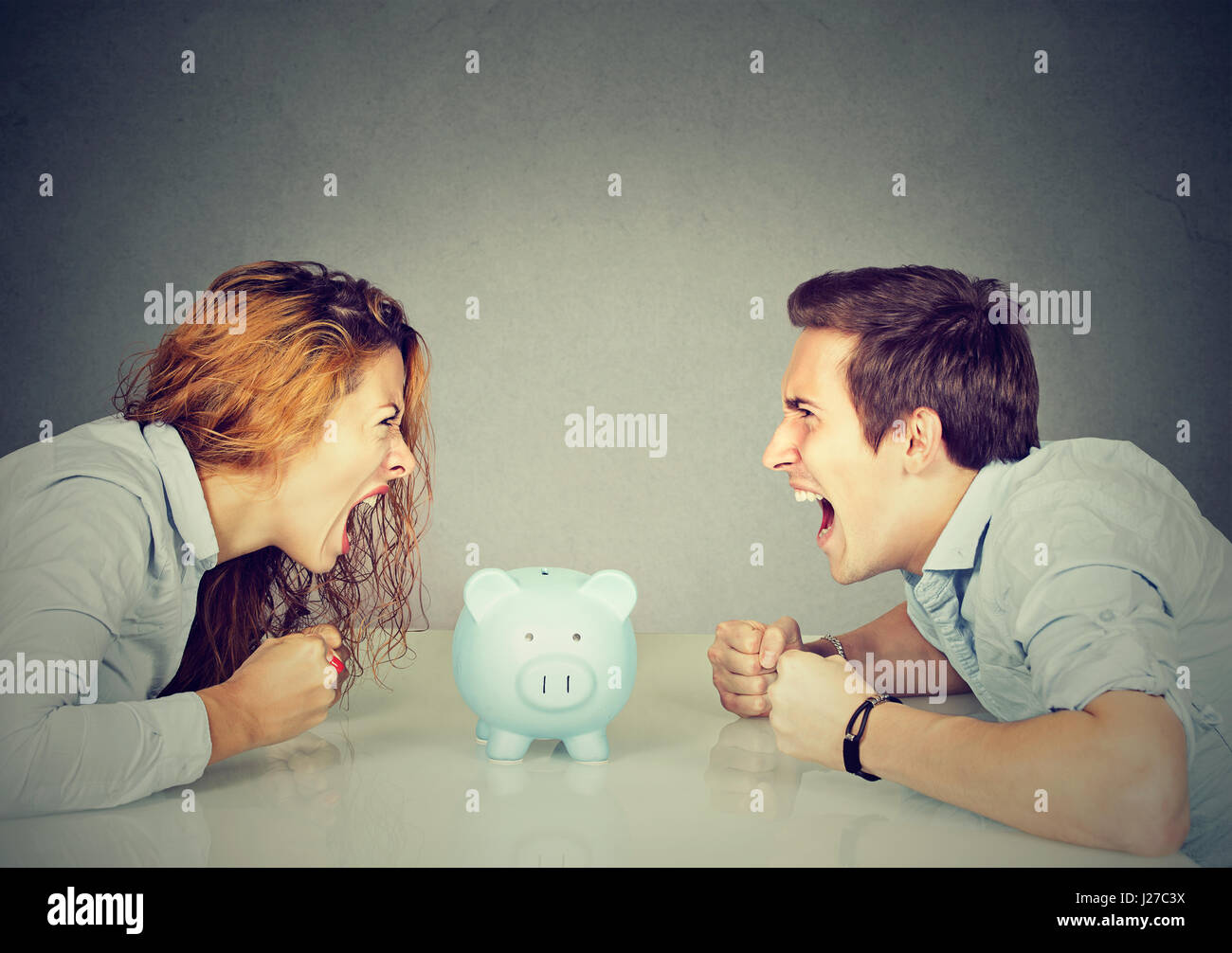 Finances in divorce concept. Wife and husband can not make settlement screaming piggy bank in-between sitting at Stock Photo