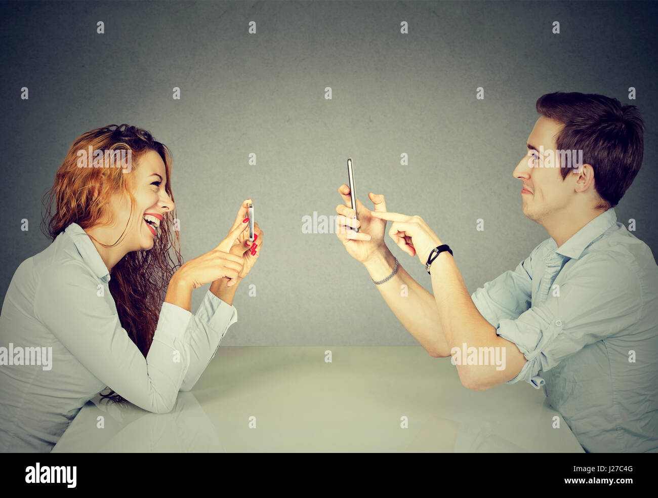 Young man and woman sitting at table using mobile phones, texting via social networks with obsessed expression or - Stock Image